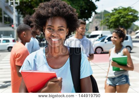 Laughing african american female student with group of friends outdoor in the city in the summer