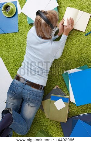 Young woman lying on floor reading book, holding onto headset, with papers all around.?