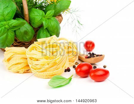 Italian pasta fettuccine nest with tomatoes and fresh basil leaves on white background