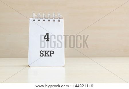 Closeup surface note book with black 4 sep word in page on blurred brown wood desk and wood wall textured background with copy space under window light