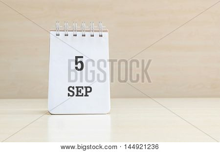 Closeup surface note book with black 5 sep word in page on blurred brown wood desk and wood wall textured background with copy space under window light