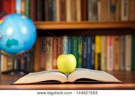 apple and book on a background bookcase