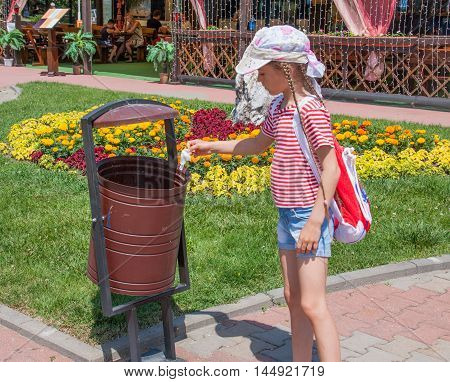 Girl throws trash into an urn in the park.