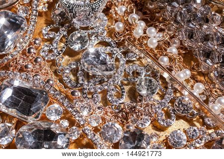 Close up of collection of assorted luxury precious golden and silver gemstone background