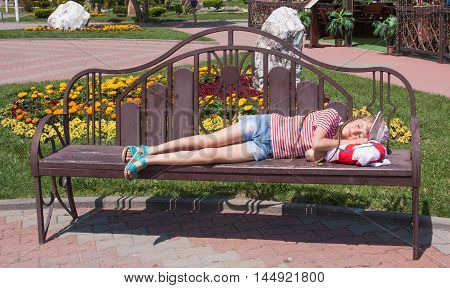 girl resting on a wooden bench in the park on a background of a lawn with flowers.