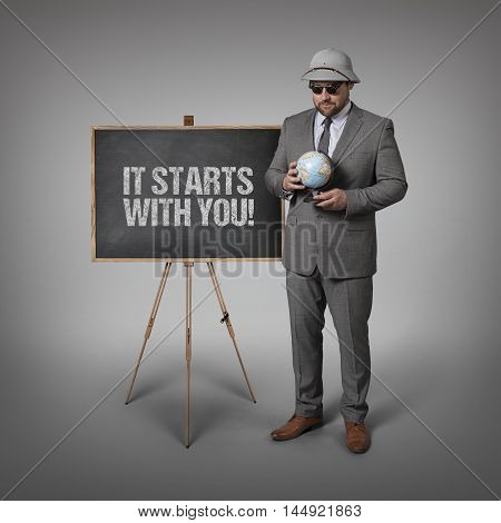 It starts with you text on blackboard with businessman and globe