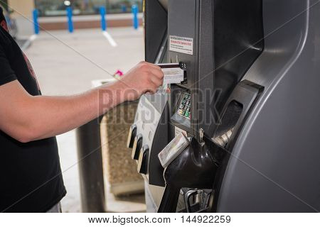 Young man using credit card at the gas pump with rising prices of gas.