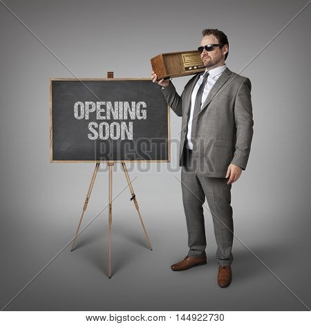 Opening soon text on blackboard with businessman holding radio