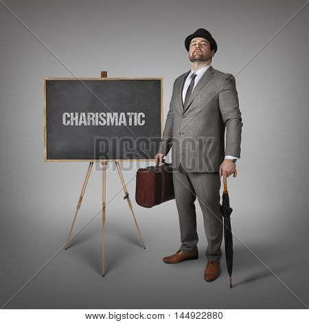 Charismatic text on  blackboard with businessman holding umbrella and suitcase