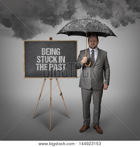 Being stuck in the past text on blackboard with businessman holding umbrella