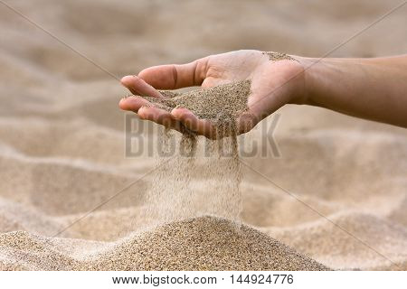 sand running through hand of woman on the beach
