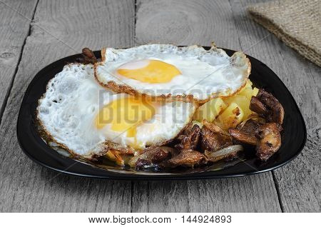Fried eggs with potatoes and mushrooms on a black plate and a rough grey Board