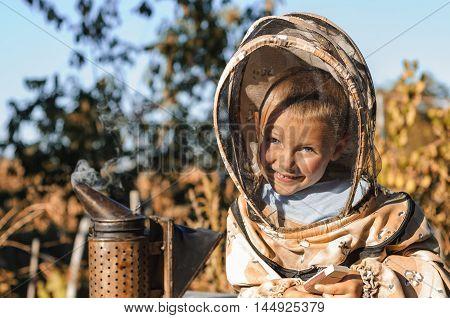 Little boy beekeeper blows smoker for bees.