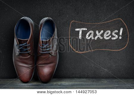 Taxes text on black board and business shoes on wooden floor