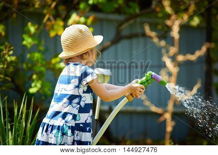 Little girl playing with water in the garden