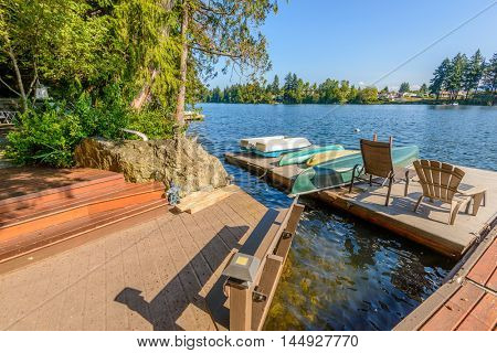 Private lake deck with chairs and boats in Vancouver, Canada.