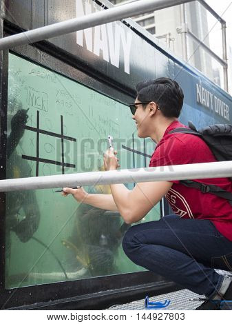 NEW YORK MAY 27 2016: An unidentified young man plays tic tac toe against a US Navy EOD technician on the glass of a 6,800 gallon mobile dive tank on Military Island in Times Square during Fleet Week.