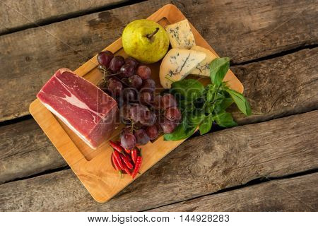 Raw meat on a board. Grapes and pear. New recipe of meat dish. Best sort of pork.