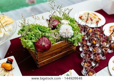 Decor of natural vegetables and fruit on a table, standing in a wooden box and decorated with flowers. Close-up