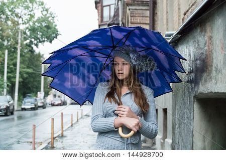 Sad beautiful young woman in a knitted hat standing under an umbrella in the rain on a city street