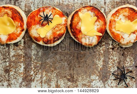 Halloween snack - pizza with tomato sauce and cheese on old metal background top view empty space for text