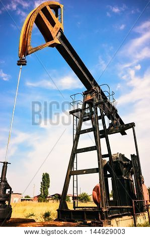 Oil derricks at oil and gas field over blue sky with clouds closeup in Bulgaria Europe