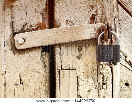 Old closed weathered wooden door with the padlock on it