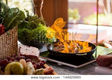 Flames in pan. Meat and garlic being fried. Recipe of flambe steak. Hot and spicy.