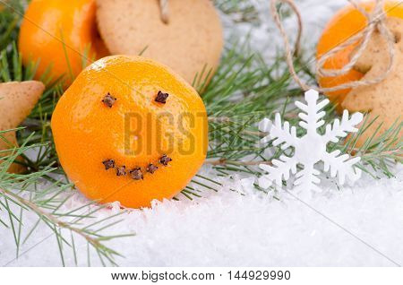 Christmas decorations tangerine and ginger biscuits in the snow among the fir branches