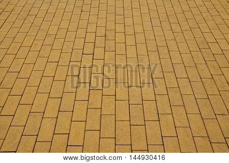 Sidewalk paved with yellow tiles. Beautiful background
