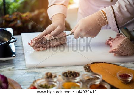 Knife is cutting raw meat. Cook's hands in gloves. Chef is cooking pork. Ingredient of high-calorie dish.