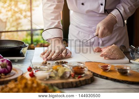 Hand touches raw meat. Chef stands near the table. Restaurant cook prepares pork. Use only fresh ingredients.