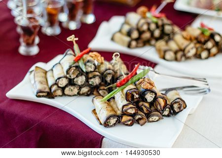 Fried zucchini with stuffing, delicious rolls laid out on white plates and garnished with peppers