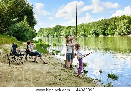 family camping and fishing, people active in nature, child caught fish on bait, river and forest, summer season