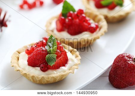 Dessert Tartlets With Berries On White Wooden Background