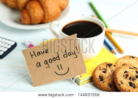 Piece of note paper with cup of coffee and cookies on blue wooden background, have a good day