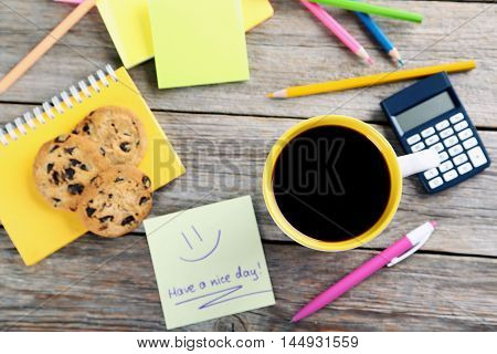 Piece of note paper with cup of coffee and cookies on grey wooden background, have a nice day