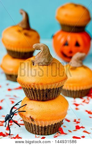 Homemade Halloween pumpkin chocolate cupcakes on blue background for trick or treat night selective focus