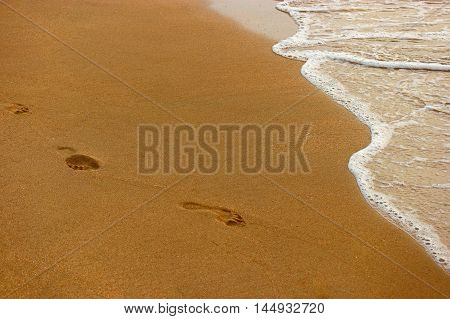 Sandy beach, wave and footsteps backlit in sunset time.