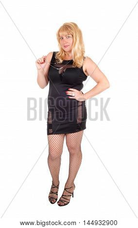 A beautiful woman in her forties standing in a black evening dress and black stockings isolated for white background.