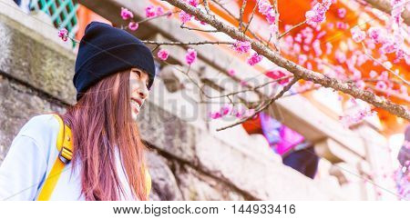 Female Japanese Teenager with Pink Blossom plum copy space