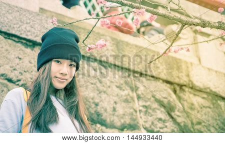 Japanese Teenager in temple with plum flower blooming