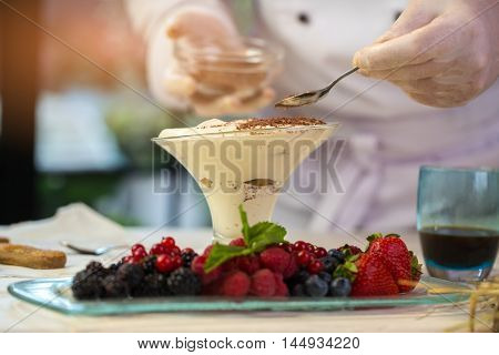 Glass filled with cream. Hand holding a small spoon. Chocolate crumbs for tiramisu. Dessert made of organic ingredients.