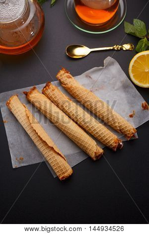Waffle Tubules With Condensed Milk And Fresh Hot Tea And Lemon Over Black Background