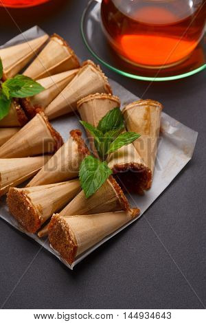 Homemade Honey Wafers Rolled Into A Cone, Filled With Condensed Milk, A Cup Of Tea On A Black Table