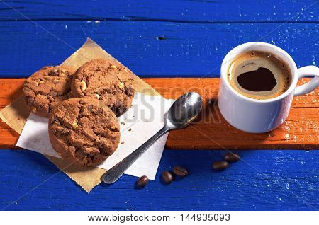 Cup of hot coffee with chocolate cookies on colorful wooden table