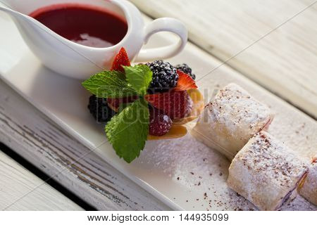 Dessert with berries on plate. Tartlet near jug with sauce. Rolls with sweet filling. Well-decorated dish.