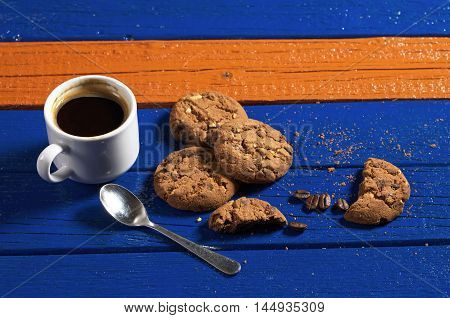 Chocolate cookies with cup of hot coffee on colorful wooden table
