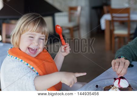 Laughing Child Sharing Chocolate Cake With Mother