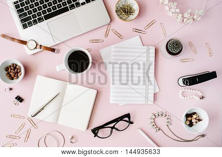 Flat lay top view office table desk. feminine desk workspace with succulent laptop glasses diary and golden clips on pink background.